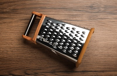 Modern grater on wooden table, top view