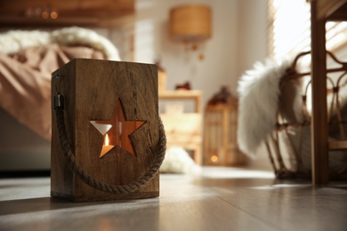Decorative wooden lantern with burning candle in cozy bedroom, space for text. Interior element