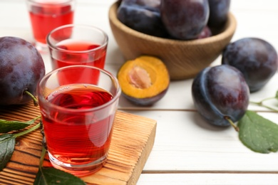 Delicious plum liquor and ripe fruits on white wooden table, closeup. Homemade strong alcoholic beverage