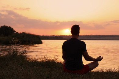 Man meditating near river at sunset, back view. Space for text
