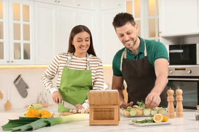 Happy couple making dinner together while watching online cooking course via tablet in kitchen