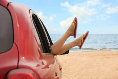 Woman showing legs from car, closeup. Summer vacation trip