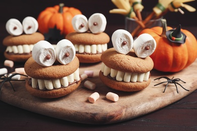 Delicious Halloween themed desserts on wooden table, closeup
