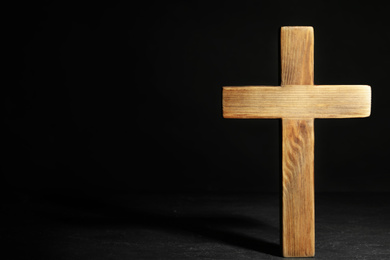 Wooden Christian cross on black slate table against dark background, space for text. Religion concept