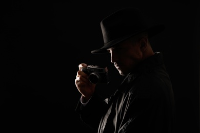Old fashioned detective with camera on dark background. Space for text