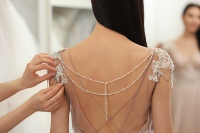 Woman trying on beautiful wedding dress in boutique, back view