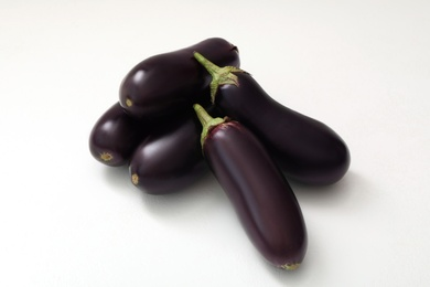 Pile of raw ripe eggplants on white table