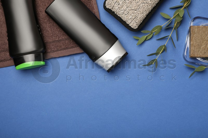 Flat lay composition with shower gel bottles on blue background, space for text