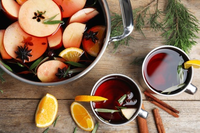 Tasty mulled wine with spices on wooden table, flat lay
