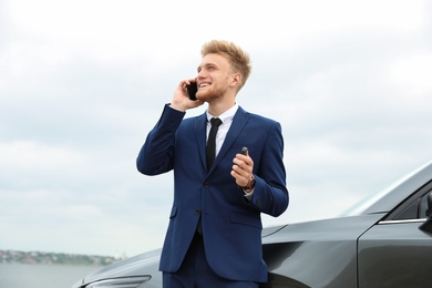 Young businessman with key talking on phone near car outdoors