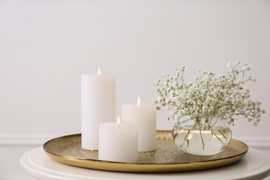 Vase with beautiful flowers and burning candles on table indoors. Interior elements