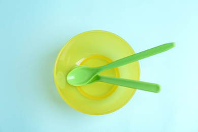 Small bowl and spoons on light blue background, top view. Serving baby food