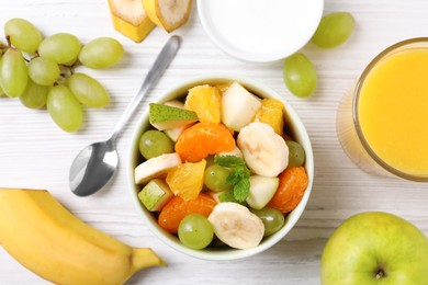 Delicious fresh fruit salad in bowl on white wooden table, flat lay