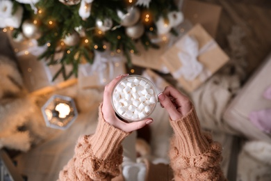 Woman with cup of delicious hot drink near Christmas tree at home, top view