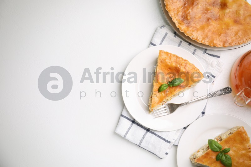 Delicious pie with meat and basil on white table, flat lay. Space for text