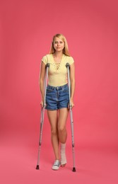 Young woman with axillary crutches on pink background