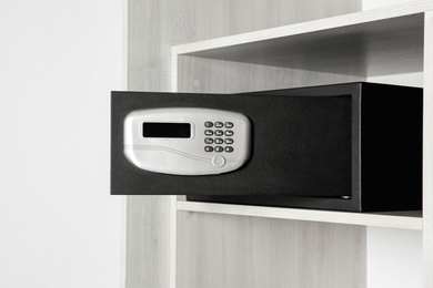 Black steel safe with electronic lock in wooden closet