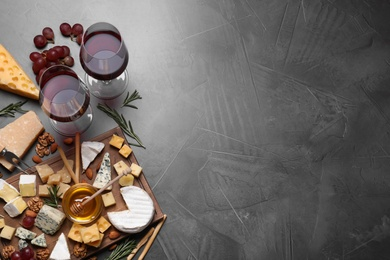Cheese plate with honey, grapes and nuts on grey table, flat lay, Space for text