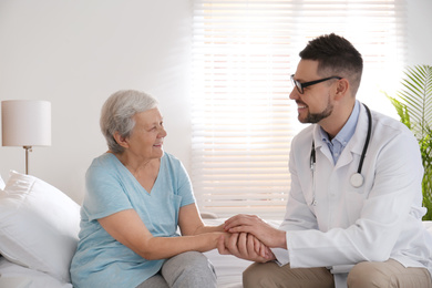 Doctor visiting senior patient in modern hospital