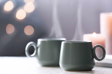 Cups of hot drink on white table against blurred background, space for text