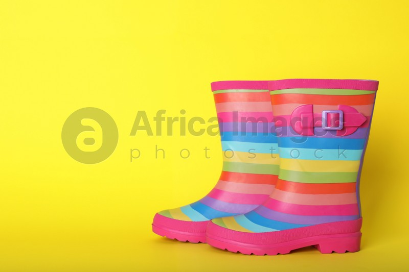 Pair of striped rubber boots on yellow background. Space for text