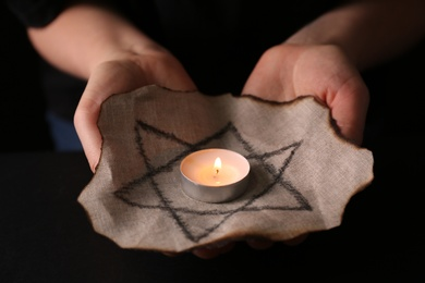Woman holding fabric with star of David and burning candle on black background, closeup. Holocaust memory day