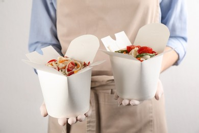 Chef holding boxes of vegetarian wok noodles on light background, closeup