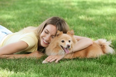 Young woman with her cute dog on green grass in park
