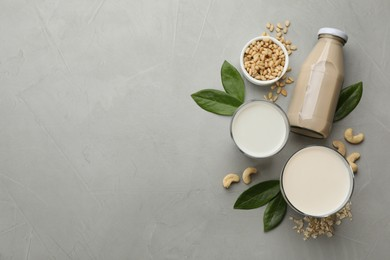 Different vegan milks and ingredients on light grey table, flat lay. Space for text