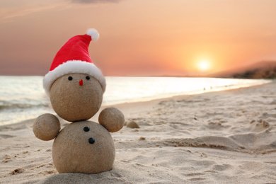 Snowman made of sand with Santa hat on beach near sea at sunset, space for text. Christmas vacation