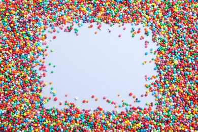 Frame of colorful sprinkles on light grey background, flat lay with space for text. Confectionery decor