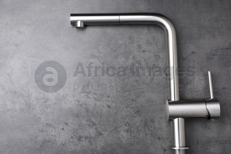 Modern pull out kitchen faucet on grey table, top view. Space for text