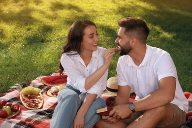 Lovely couple having picnic on plaid outdoors