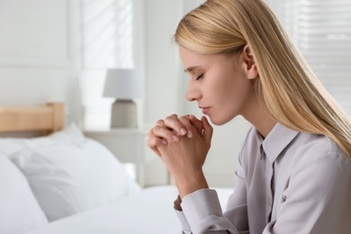 Religious young woman praying in bedroom. Space for text