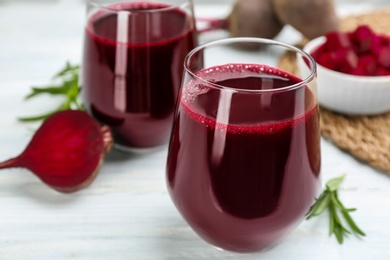 Fresh beet juice and raw vegetable on white table, closeup