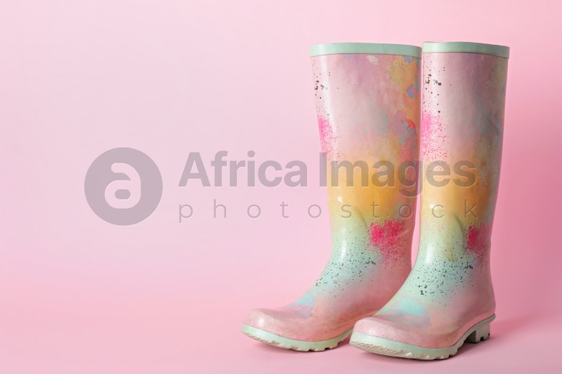 Pair of colorful rubber boots on pink background. Space for text