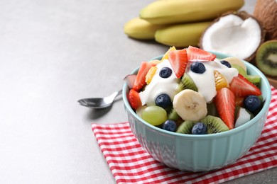 Delicious fruit salad on grey table. Space for text