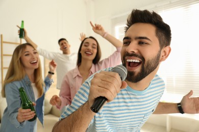 Young man singing karaoke with friends at home