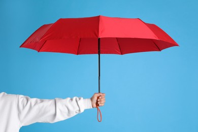 Woman with open red umbrella on light blue background, closeup