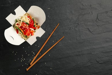 Box of vegetarian wok noodles with chopsticks on slate table, flat lay. Space for text