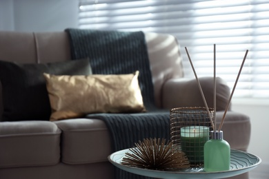 Air reed freshener, candle and decor element on table in living room. Space for text