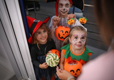 Cute little kids wearing Halloween costumes and trick-or-treating at doorway