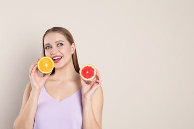 Young woman with cut orange and grapefruit on beige background, space for text. Vitamin rich food