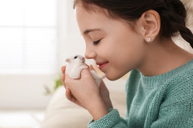 Little girl with cute hamster at home