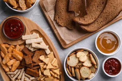 Different crispy rusks and dip sauces on light marble table, flat lay