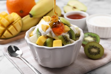 Pouring honey onto delicious fruit salad in bowl on table