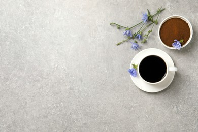 Cup of delicious chicory drink, powder and flowers on light grey table, flat lay. Space for text
