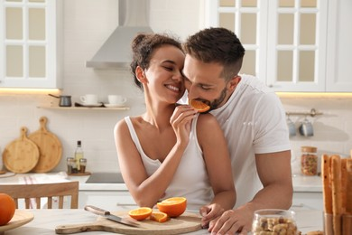 Lovely couple enjoying time together during breakfast at table in kitchen