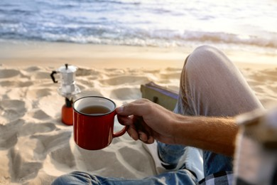 Man with cup of hot drink on sandy coast, closeup. Beach camping