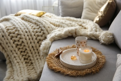 Cup of drink and burning candles on sofa in room, space for text. Interior elements